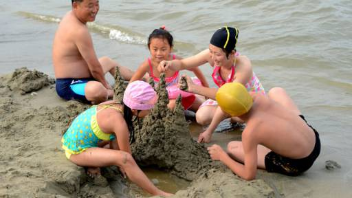 A family builds a sandcastle