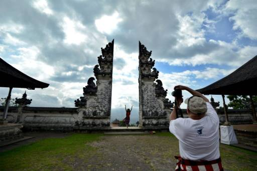 Tourists take photos by an arch on the Lempuyang Temple grounds as Mount Agung volcano is seen obscured by clouds in the background in Karangasem on Bali island on Oct. 4, 2017.